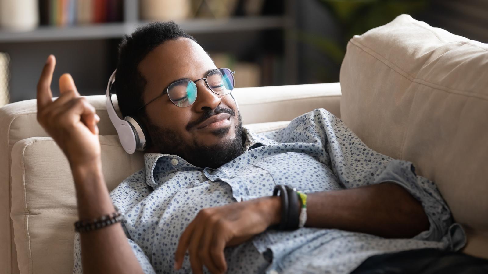 Người hạnh phúc nằm trên ghế nghe nhạc bằng tai nghe không dây